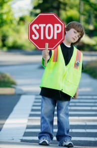 Portrait of a young boy crossing guard standing on the road holding a stop sign